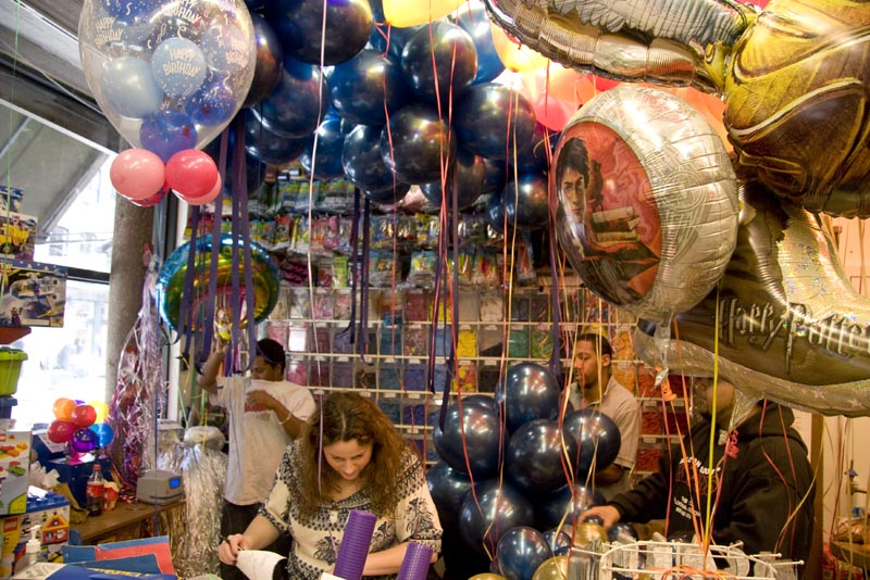 A Balloon Saloon staff member working behind the counter