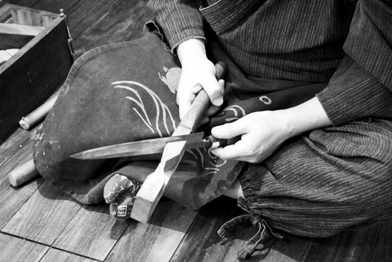 A seated view of handwork being performed on a knife blade at Korin Japanese Trading, Corp